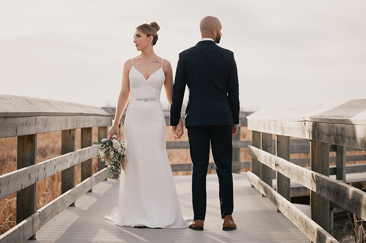 bride and groom posing on wooden pathway